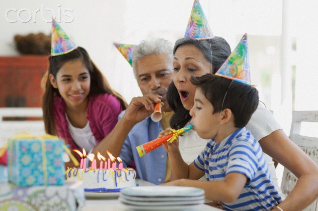 Family blowing out candles with noisemakers.